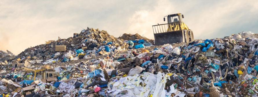 A yellow front end loader drives over a pile of garbage in a landfill