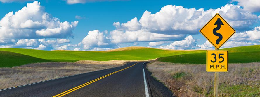 paved country road with green fields on both sides and beautiful blue sky with white puffy clouds