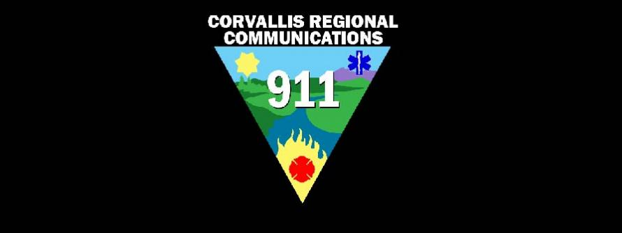 Corvallis Regional Communications Center 911 logo (black triangle with fire, sun, medical signs in each corner and 911 in the middle).