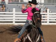 Rodeo pageant contestant waving at the crowd riding her black and white Paint horse.