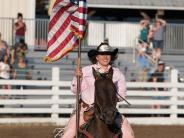 Queen raising the American Flag from her horse, at the start of the 2018 Benton County Fair & Rodeo.