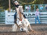 Lady roping contestant riding her Palomino horse in the calf roping event.