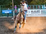 Lady contestant calf roper, stepping off her Buckskin horse.