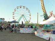 Picture of a ferris wheel and ring of fire rides at the fair