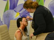 Volunteer getting made up for multi-agency disaster drill.