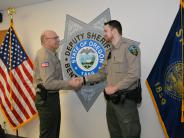 Undersheriff Ridler congratulates new Corrections Deputy Garrison.