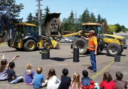Erik Remington, Public Works staff, showing off a mower and backhoe to Hoover Elementary School students.