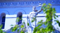 statue of lady justice on top of a courthouse