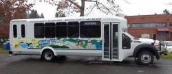 """A white Coast to Valley bus with painted mural of """"Coast to Valley"""" in green and blue."""