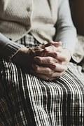 An elderly woman holds her hands in her lap.