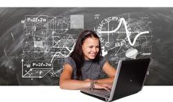 A young female is in front of her computer, sitting in front of a blackboard with calculations and charts written in white chalk.