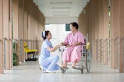 A female nurse dressed in blue looks up at her patient wearing a pink robe who's sitting in her wheelchair.