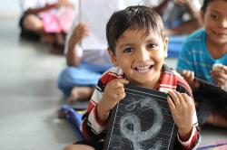 little boy with hand held chalk board smiling