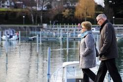 A male and female adult over the age of sixty walk next to a marina, wearing heavy coats and scarfs.