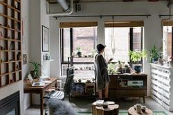 A middle aged female walks around her office and gazes out her office window.