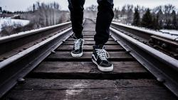 a person walking a set of railroad tracks, all you can see is their knees down walking towards you.